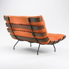 MARTIN EISLER AND CARLO HAUNER    lounge chair and ottoman    Forma  Italy, c. 1955  stained oak, enameled steel, rubber  27.25 w x 31 d x 32 h inches  Ottoman measures: 27.25 w x 21.75 d x 14.5 h inches