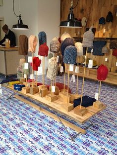 Different lengths of wooden poles in wooden bases to display knitted hats.