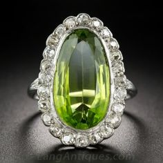 Expertly hand-fabricated in platinum, this singular Edwardian treasure glistens and glows with an unusually cut, elongated, asymmetrical oval peridot, weighing 7.45 carats. The luscious lime green gemstone is framed with old mine-cut diamonds supported by a contrasting 18K yellow gold gallery.