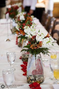 Red floral centerpieces with stones on the bottom of the vase
