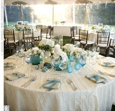 Kim and Jim's florist used five small centerpieces featuring round blue vases and white flowers, which surrounded a large clear hurricane filled with aqua-tinted rocks and a large candle.