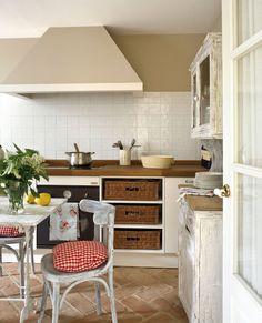 Cestos de mimbre en la cocina  La encimera de madera, diseñada por Memi Escarzaga tiene debajo cestos de mimbre de Ikea.