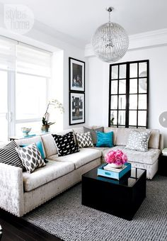 Contemporary condo Playing off a black-and-white palette, designer Stacey Cohen adds sparkle through a gorgeous orb light fixture and silver nailhead detail she added to the sofa. The turquoise accents around the room are vibrant and playful, and give the living room that perfect pop of colour.