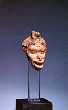 A Late Hellenistic Terracotta Head of a Grotesque with a Top-knot, Exceptionally Fine Style. 1 Century BC-1st Century AD. In late Hellenism genre sculpture developed. The range of subjects including not only dwarves and individuals with unusual faces or deformed bodies, but also comic characters draw from the theatre as well as fishermen and Nubians emerged.