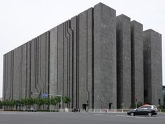 =A dark gray block-like building towering over an intersection, with narrow, sometimes diagonal cracks in one side and large gaps in the other