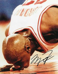 """THIS RARE PICTURE HERE IS PROBABLY THE GREATEST BASKETBALL PLAYER TO EVER LIVE AND THIS IS MICHAEL JORDAN WHO WON 6 CHAMPIONSHIPS WITH THE CHICAGO BULLS AND MANY, MANY DIFFERENT INDIVIDUAL AWARDS DURING HIS CAREER AND THIS PHOTO IS JORDAN I BELIEVE MIGHT HAVE BEEN HIS LAST HOME GAME IN CHICAGO GOING TO THE CENTER OF THE COURT WITH THE SACRED BULLS LOGO AND LEANING DOWN TO KISS A TREASURED LOGO THAT HE WILL """"FOREVER CHERISH IN HIS HEART"""" FOR THE REST OF HIS LIFE"""