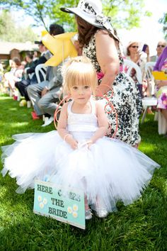 Flower girl in tutu, with sign, and her own chair!