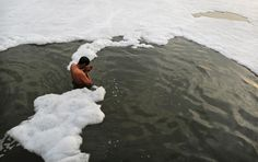 An Indian Hindu devotee prays in a polluted section of the Yamuna River, holy to Hindus, on the outskirts of New Delhi, India, on March 10, 2013. Officials say factories are ignoring regulations and dumping untreated sewage and industrial pollution, turning toxic the river that gives the capital much of its drinking water.