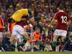 Aufgegabelt: Der Australier Israel Folau wird von seinem Gegespieler George North von den Lions bei einem Rugby-Test in Melbourne weggetragen. (Foto: Mark Dadswell/dpa)