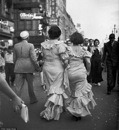 A couple of well-dressed ladies circulate through the crowd during Mardis Gras festivities in New Orleans 1937