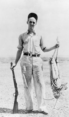 Unidentified man holding a rifle posed with his bag - a 3 foot grasshopper.