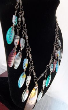 From Luulla.com Dee-Liteful Jewelry Creations One of a kind ~ Fishing Lure Necklace. This necklace is made from all fishing items.The chain is made from #5 swivels. The lures are multi-colored and iridescent. The pendant is a spoon lure that has been fired and tarnished to create the discoloring.The necklace is 20 inches long.