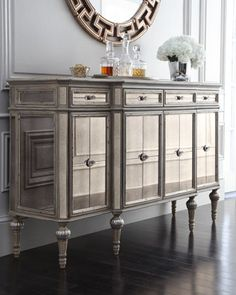 "Dresden Four-Door Mirrored Console  Reflective console with multiple storage options. Made of hardwood with an antique-cream finish, silvery accents, and mirrored insets. Four drawers; four doors; four adjustable shelves (one behind each door). 64""W x 19""D x 39""T. Imported. Boxed weight, approximately 241 lbs.  More ▾  Dresden Four-Door Mirrored Console  Compare At: $2,399.00 Special Value: $1,439.00"