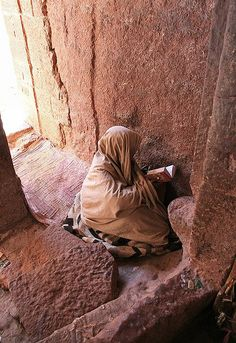 Reading the Bible, inside Lalibela churches area, Ethiopia. Lalibela is a town in northern Ethiopia that is famous for its monolithic rock-cut churches. Lalibela is one of Ethiopia's holiest cities, second only to Aksum, and is a center of pilgrimage for much of the country. (V)