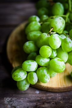 Vine of green grapes on rustic wooden background by Alena Haurylik on 500px