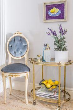 Brass and glass bar cart aside a velvet powder blue vintage inspired chair.
