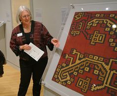 Peggy Greenwood points out features of a late Nasca style Peruvian handwoven textile. Photo by Candace Edgerley