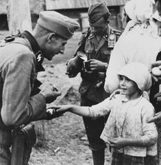 The Waffen-SS is warmly received by Ukrainians and presented with refreshments and food. This photograph was taken in the summer of 1941 and the men are possible from the Wiking Division.
