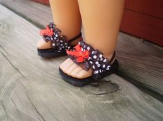 These shoes are handmade of black foam for the base and black felt overlay with a black satin ribbon around the side of the shoes. Across the shoe is Black white polka dot ribbon with a red bow on front and the shoe has black elastic to go around the ankle.