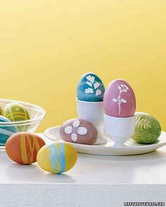 "Masked Designs | Martha Stewart Living - Adhere common supplies such as tape, stickers, or even little leaves to eggs; when you dye the eggs and remove the ""masks,"" the designs stand out."