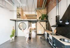 To prevent the unit from feeling too dark and cramped, the studio suggested adding a mezzanine rather than a full floor. Black And White Tiles, White Walls, Madrid Apartment, Metal Kitchen Cabinets, Open Living Area, Steel Columns, Industrial Apartment, Up House, Interior Decorating