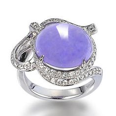 A jadeite and diamond ring |  Set with a rich lavender oval jadeite cabochon, within an undulating ribbon surround set with round brilliant-cut diamonds and white gold.
