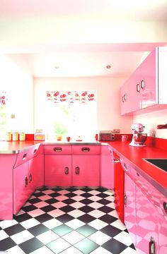 Pink cupboards, red countertop, and black and white kitchen floor