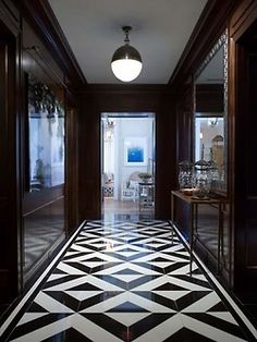Very very chic, and surprisingly dark and masculine, foyer by Phoebe Howard. Love the glossy wood panelled walls, graphic black and white tile floor, and single hicks pendant.