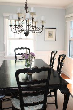 Dining - taller white wainscotting w/ shelf and long curtians that take up back wall/window, blue walls and black table & chairs