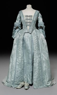 An 18th century Watteau Pleat/Sack Back Robe and matching Petticoat, circa 1775, of eau-de-Nil damask, the open robe with self fabric trimming to front opening, self fabric flounce to petticoat, together with a pair of matching self-fabric covered shoes with Louis heels, pointed toes and lachets.
