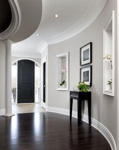 light gray walls, white trim, dark floors in this stunning foyer