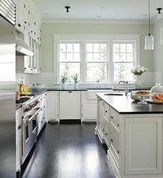 a life's design: apron front sink, white shaker style cabinets, dark wood floor, dark countertops (soapstone??)