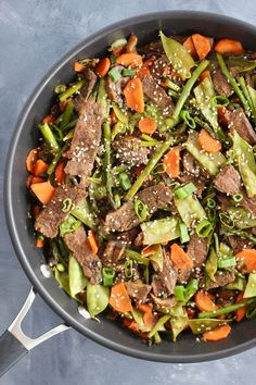 Incorporate seasonal ingredients like carrots, peas, and asparagus into this super quick Vegetable and Flank Steak Stir Fry. A perfect protein and veggie-packed recipe to whip up for your next meal. #seasonal #healthymeal #stirfry