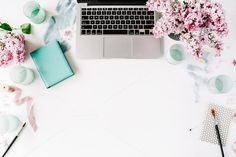 Flay lay composition for bloggers, artists, magazines and social media. Workspace with paintbrush, laptop, lilac flowers bouquet, spool with beige and blue ribbon, mint diary on white background.