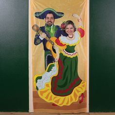 Fiesta Couple Photo Door Banner. Hang this plastic banner at your fiesta celebration for a fun photo opportunity! Your guests will love becoming a mariachi dancer with this festive decoration. A cute idea for a fiesta party or Mexican-themed school dance! 3 ft. x 6 ft. © OTC