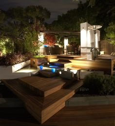 A modern garden deck at night in Melbourne by TLC Pools & Landscape