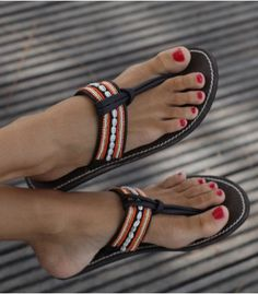 The colour of a beautiful sunset, the Sara sandal is an elegant and a stylish sandal with its warm colours, small shells and leather details. Show them off with bare legs and a mini skirt.  Handmade in Kenya.  Thong style sandal.  Genuine leather upper (dyed  sun dried) with contrasting white stitching.  Flat flexible rubber sole (0.4).