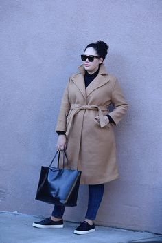 camel coat, black sweater, black sneakers, jeans