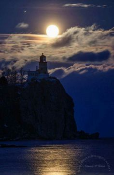 Breath taking!  I love how the moon and clouds show the lighthouse and light on the water.
