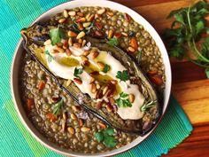 This dish of eggplant roasted until caramelized and tender, served over stewed lentils with an extraordinarily light and creamy tahini sauce and crunchy pine nuts, was dinner and lunch for more meals than I care to count a couple of weeks back. Not that I'm complaining: It's extremely good.