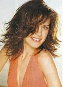 Cute Medium Length Hairstyle.  The Length rests just below the shoulders, and TONS of Layers are cut through-out the interior.  A Bang is angled off to the side and Blended down the Length of the Sides to the ends (Face-Framed).  Apply Volumizing serum to damp hair and blow-dry the hair about 80% dry.  Divide hair into smaller sections and then blow-dry each section with a medium barrel round brush in an upward motion (Opposite of Under).  Blow-dry the sides and bang with the Round Brush…