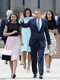 The girls are pictured with their father President Barack Obama and mother First Lady Michelle Obama arriving at the airport to greet the Pope