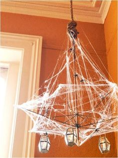 The frame from a broken umbrella becomes a haunted chandelier frame when decorated with webs, spiders, and mini lanterns.