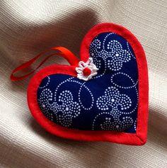 Modrotiskové srdce 2 Šitá ozdobička z modrotisku ve tvaru srdíčka, s krajkovou aplikací ve tvaru kytičky s červeným knoflíčkem, obšita červeným šikmým proužkem. Červená stužka k zavěšení. Velikost ozdobičky 8 cm.