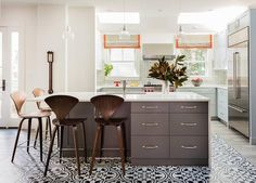 Three glass pendants hang over a dark gray kitchen island wrapped with a white quartz waterfall countertop fitted with a stainless steel sink lined with Cherner Bar Stools atop a black and white mosaic tiled floor.