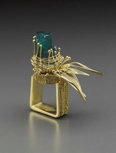 Arline M. Fisch (born1931)  Ring,  Square gold shank with applied woven design, surmounted by circular textured bezel. Above is woven nest containing synthetic Chatham emerald crystals. Further highlighted by protruding leaves and stems.   Bague, or18kt, partiellement tissé,  émeraudes synthetiques.