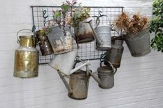 """""""Grand Scale  This watering can collection has been amassed over the years, giving a small courtyard a quirky yet interesting focal point. Published: SA Garden and Home: January 2008, Text: Melanie Walker, Photograph: Connall Oosterbroek """""""