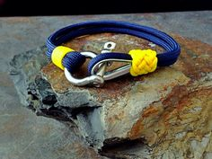 Michigan Wolverines Nautical Bracelet Paracord Bracelet With Stainless Steel Shackle & Thimble Clasp With Whipped End And Gaucho Knot.    ~~~~~~~~~~~~~~~~~~~~~~~~~~~~    All KnotOnlyParacord bracelets are handcrafted with high quality, made in the USA 550 (7 inner strands) Paracord and Type 1 Accessory Cord (vest cord.) ~~~~~~~~~~~~~~~~~~~~~~~~~~~~    This Michigan Wolverines Nautical Bracelet is made with a stainless steel shackle and thimble for the clasp. A Gaucho Knot has been added…