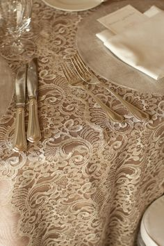 Dress It Up: Gorgeous layered cream lace over pale grey table linens. The dishware offers an additional texture.