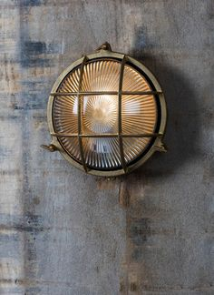 Add a touch of nautical inspiration outdoors with the Devonport Round Bulk Head Light in Brass
